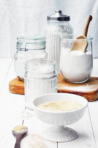 Assorted types of flour in storage jars and in a bowl