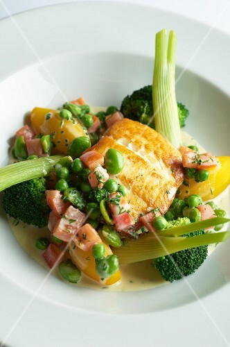 Fried halibut fillet with bacon, broccoli, peas and potatoes