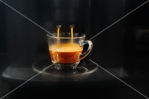 Coffee flowing from an espresso machine into a glass cup