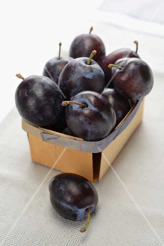Fresh plums in woodchip basket