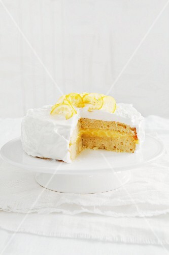Lemon layer cake on a cake stand, cut to show the centre