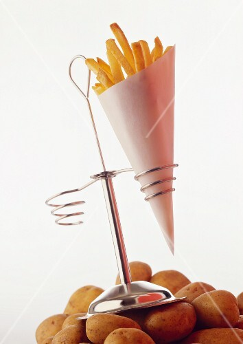 A cone of chips in a stand on a mound of raw potatoes