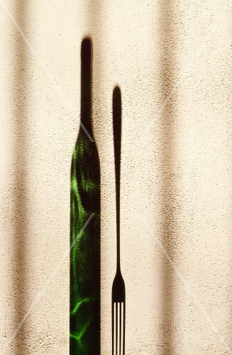 An elongated shadow of a wine bottle and a fork against the wall