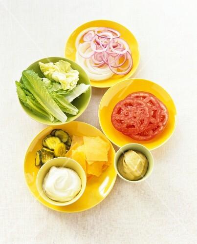Hamburger toppings in small bowls