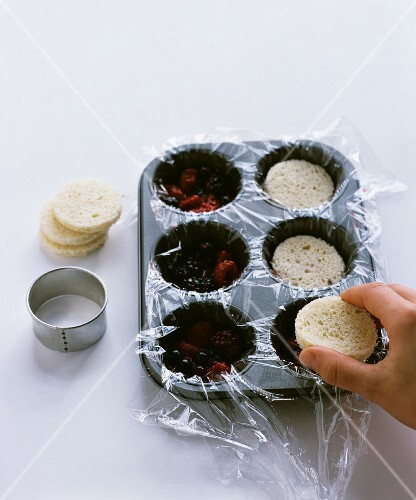 Mini summer puddings being made in a muffin tin