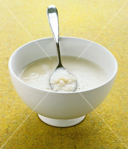 Cauliflower soup in a bowl with a spoon