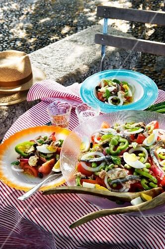 Salad niçoise on a table laid for a meal on a balcony
