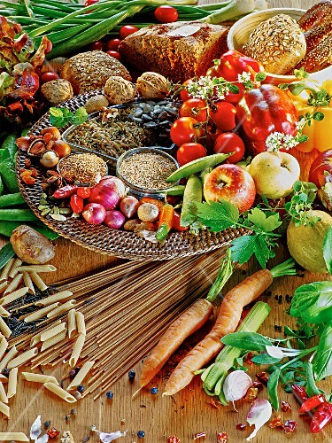 A mixed still life featuring vegetables, fruit, cereals, pasta and bread