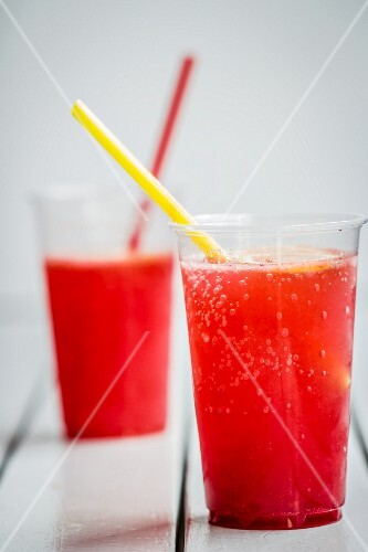 Two plastic cups raspberry syrup