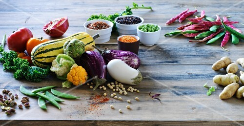 A vegetable still life featuring aubergines, pulses, squash and potatoes on a wooden table