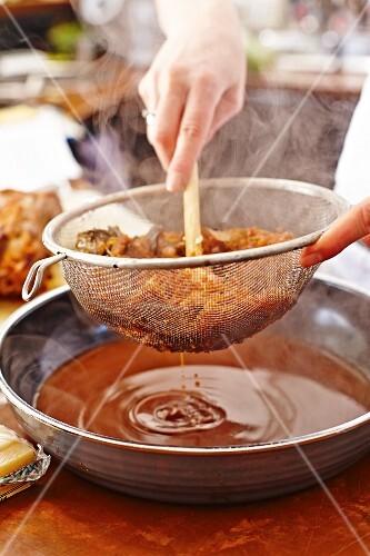 Lamb gravy being strained through a sieve