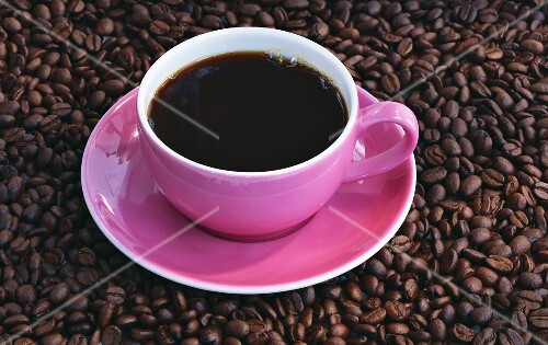 A cup of coffee on coffee beans