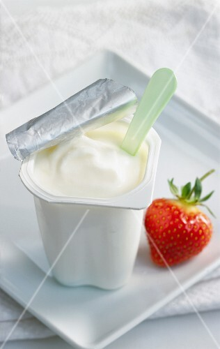 A pot of yoghurt and a strawberry