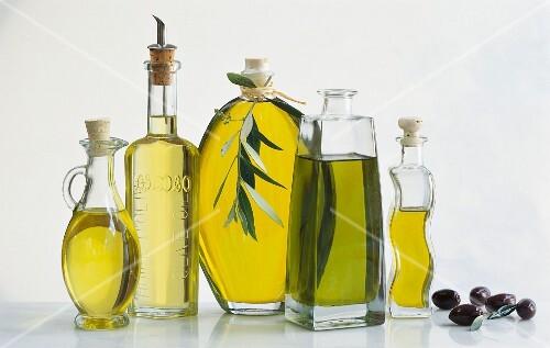Assorted bottles of olive oil and a few black olives