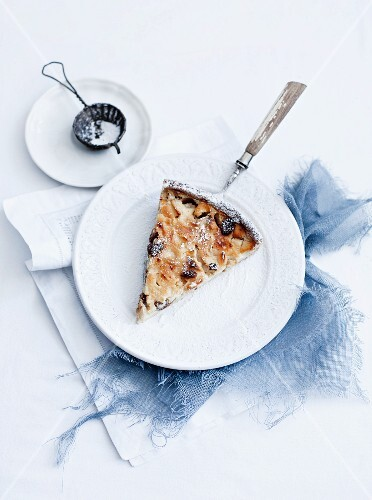 A slice of apple and quark tart with icing sugar