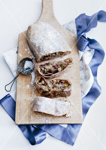 Apple strudel with icing sugar on a chopping board