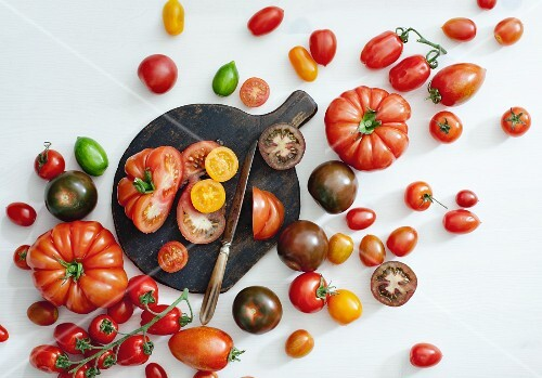 Assorted varieties of tomato, some cut in half