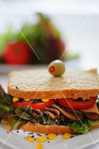 Sandwich filled with ham, tomatoes and sweetcorn