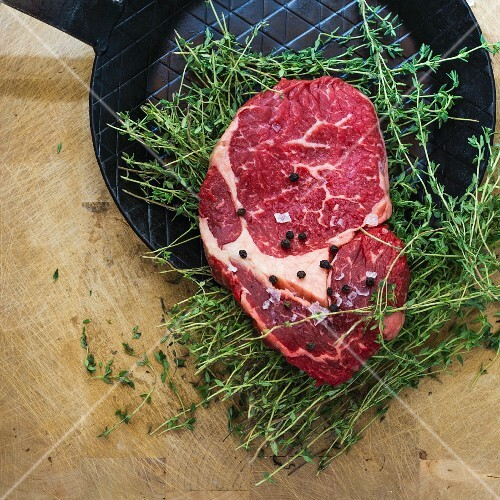Rib eye steak with thyme on a black frying pan
