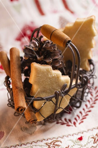A wire basket of Christmas biscuits, pine cones and cinnamon sticks