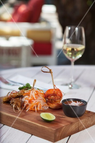 Assorted satay skewers with satay sauce on a table outdoors
