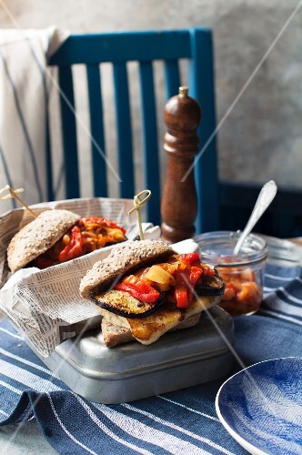 A burger bun filled with harissa, grilled vegetables and halloumi