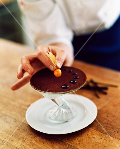 Chocolate dessert being garnished with a lychee