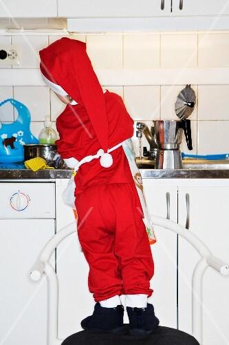 Kleiner Junge, als Weihnachtsmann verkleidet, wäscht Geschirr ab