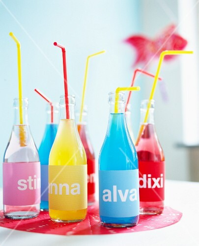 Bottles of coloured soft drinks with name labels for a child's birthday