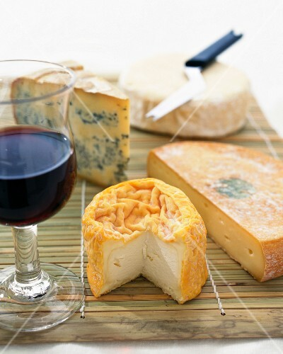 A still life of cheese and red wine