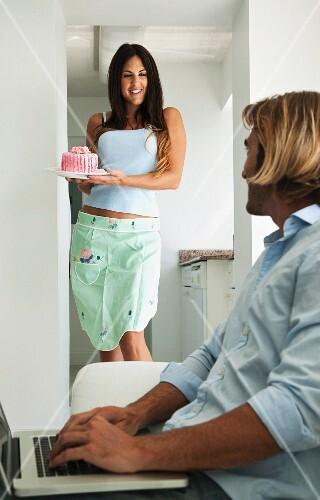 Woman showing cake to man