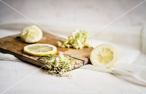Elderflowers and lemon slices on a small wooden board