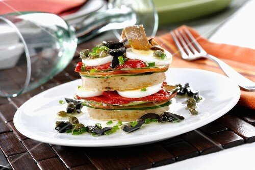 A vegetable tower with anchovies, egg and an olive and caper sauce