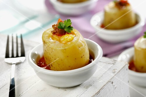 Potatoes filled with egg and ham in a tomato sauce