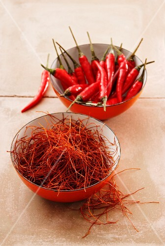 Chilli strands and fresh whole chillies in bowls