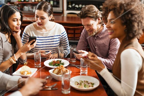 Friends at restaurant texting and showing photos using cell phones