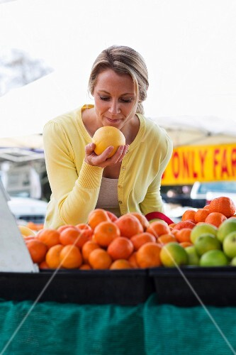 A woman with grapefruit at a vegetable stall