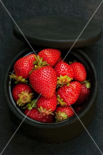 Fresh organic strawberries in a black ceramic dish