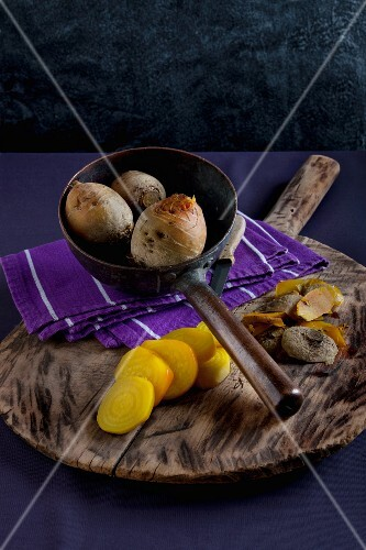 Yellow turnips, cooked, one peeled and sliced, on a wooden board and in an old metal pan, with a cloth and a knife