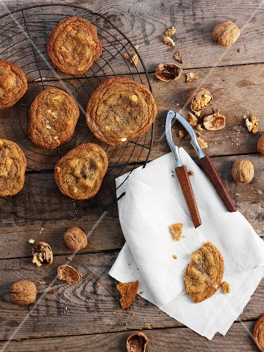 Walnut biscuits on a cooling rack, a nutcracker and walnuts