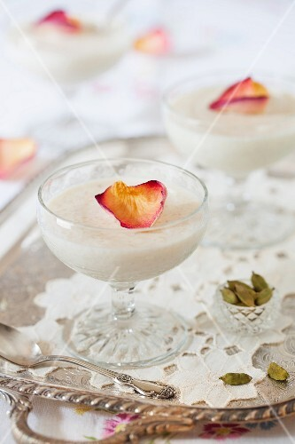 Almond rice pudding with rose petals and cardamom seeds on a silver tray