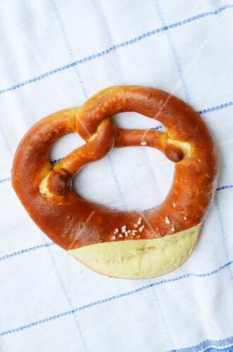 A lye pretzel on a tea towel (seen from above)