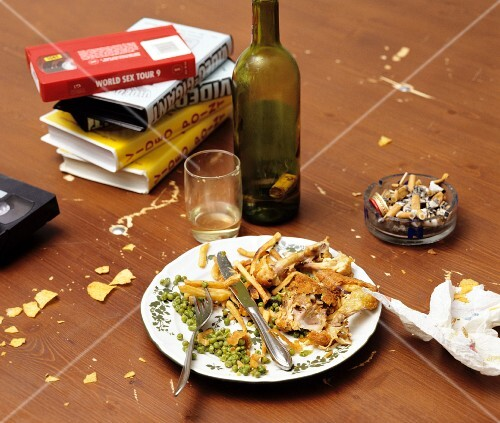 Remnants of a meal on a plate, an empty wine bottle, a full ashtray and video tapes