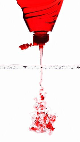 Red washing-up liquid running into water