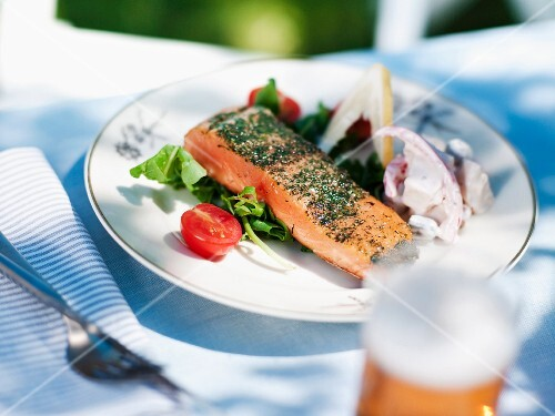 Raw spiced salmon with vegetable on plate, close-up