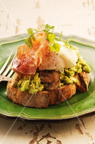 Bread topped with avocado, mushrooms, bacon and a poached egg