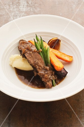 Braised beef brisket with mashed potato and vegetables