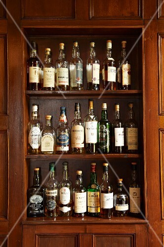 Assorted varieties of whisky on shelves on the wall