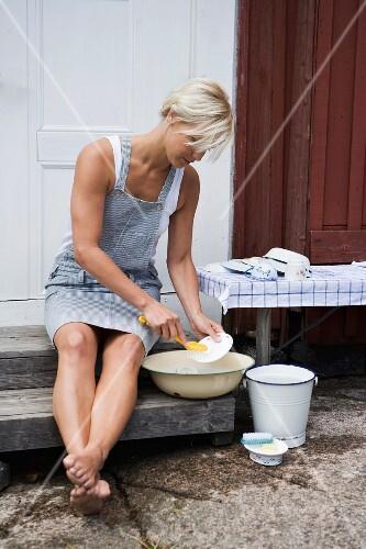 Frau macht Abwasch im Freien