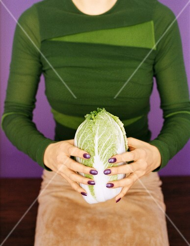 A woman holding a Chinese cabbage
